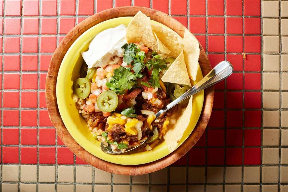 Chili served over Mexican rice with cheese, sour