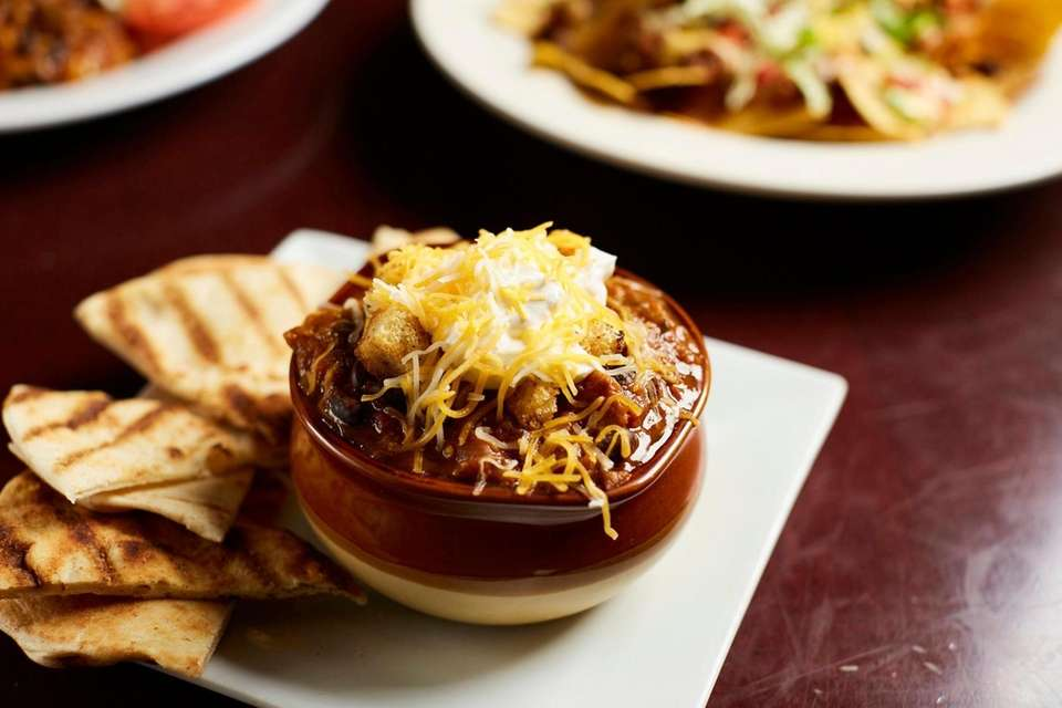 Vegetable chili topped with cheese and sour cream