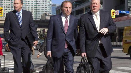 NHL commissioner Gary Bettman, center, arrives with deputy
