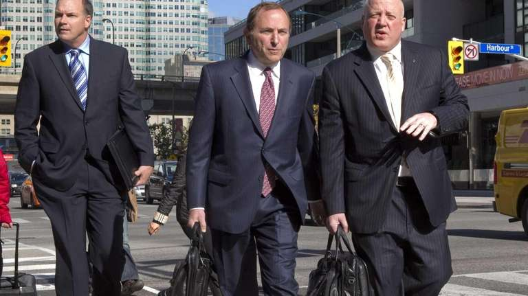 NHL commissioner Gary Bettman, center, arrives with deputy