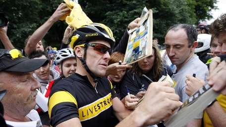 In this file phot, cyclist Lance Armstrong signs