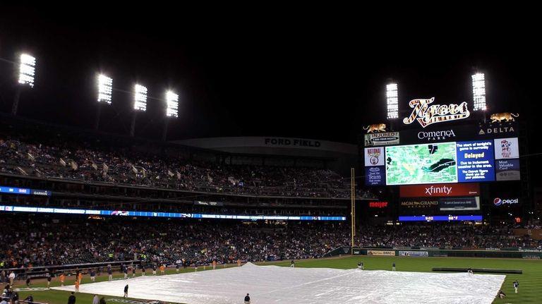 Members of the grounds crew put the tarp