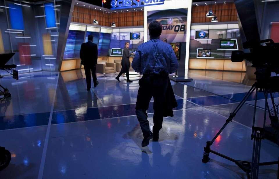 Phil Simms walks on the set of