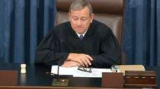 Presiding Officer Chief Justice John Roberts listens during