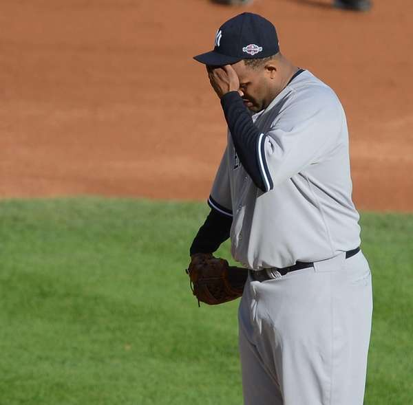 CC Sabathia wipes his face as he stands