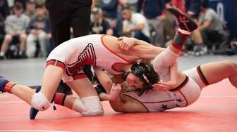 Patchogue-Medford's Steven Isselbacher wrestles Fulton's Freddy Pagan in