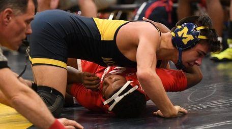 Massapequa's Anthony Conetta wrestles Freeport's Terry Ellis in