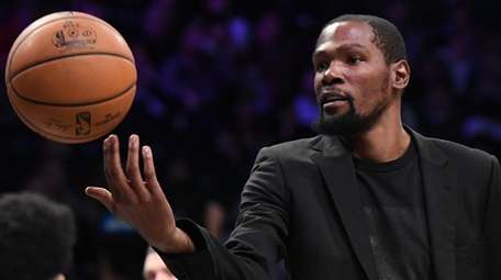 Nets' Kevin Durant tosses the ball during a