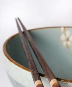 Wooden chopsticks resting on edge of ceramic bowl.
