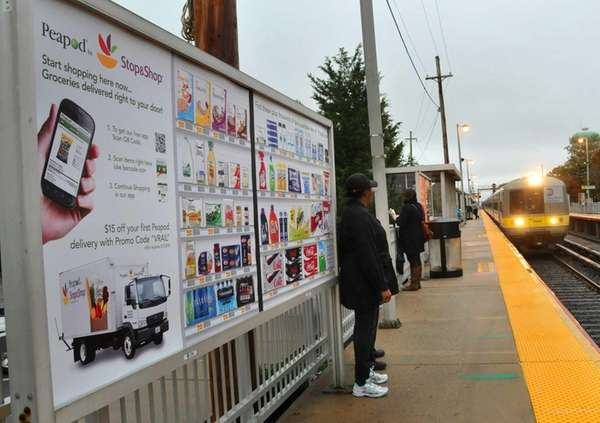 Commuters walk by a new billboard at the