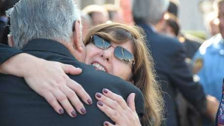 Grieving family and friends embrace after the funeral