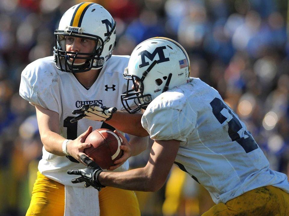 Massapequa quarterback Paul Bentz, left, hands off to