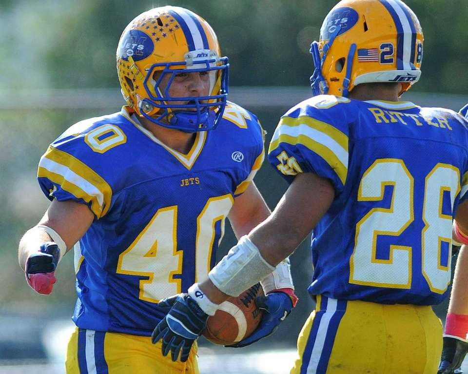 East Meadow running back Billy Andrle, left, gets