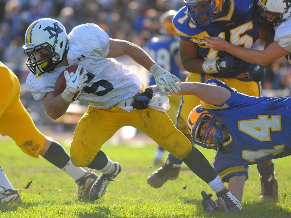 Massapequa running back Jack Korber, left, fights for
