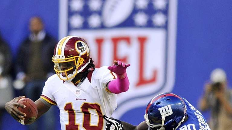 Washington Redskins quarterback Robert Griffin III is sacked