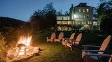 Adirondack chairs and a cozy fire await guests