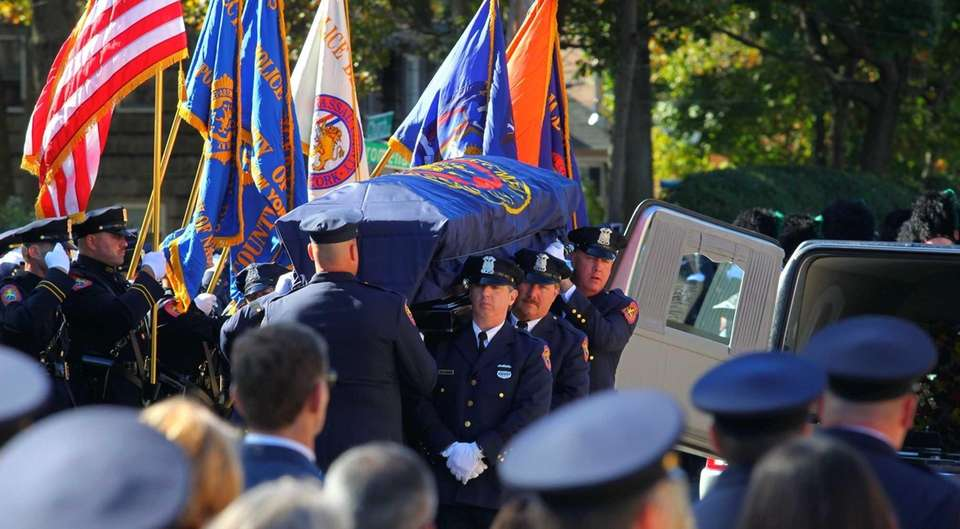 Fellow police officers carry the coffin of Nassau