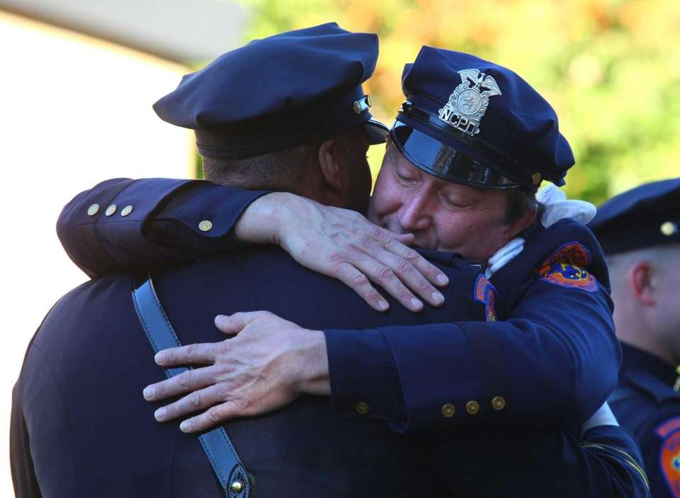 Cops console one another during the funeral of