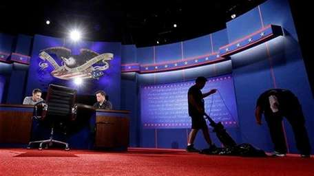 Workers prepare the set for Monday's presidential debate