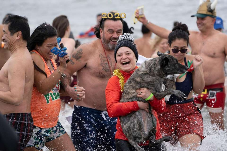 People and a dog plunge into the Atlantic