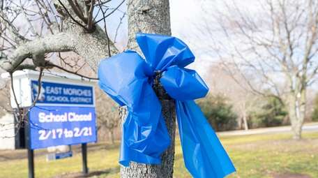 Blue ribbons are on posts, storefronts, homes and