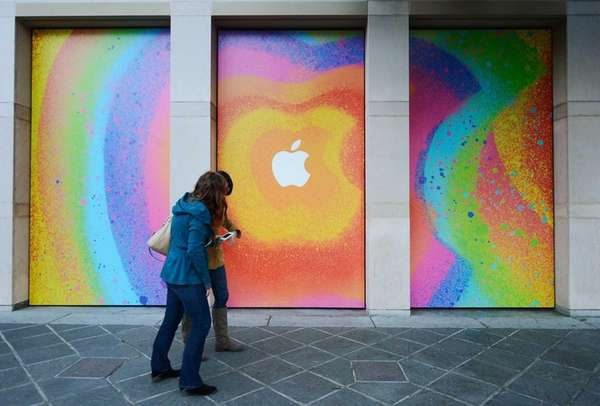Two women walk past Apple signage at the