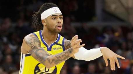 The Warriors' D'Angelo Russell passes as the Cavaliers'