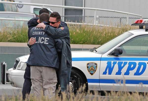 Nassau County police officers console one another outside