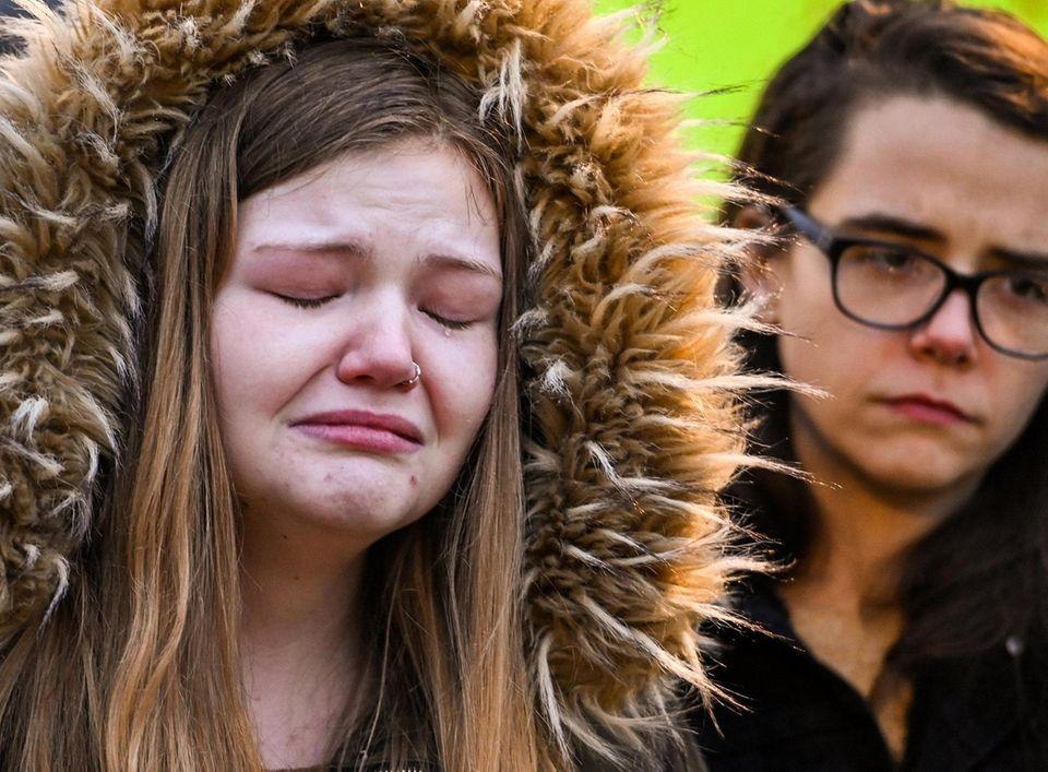 Rebecca Carr, of Mastic, left, sheds a tear