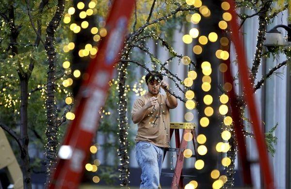 Steve Orrico strings holiday lights on Sixth Avenue