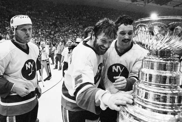 Islanders captain Denis Potvin, No. 5, reaches out