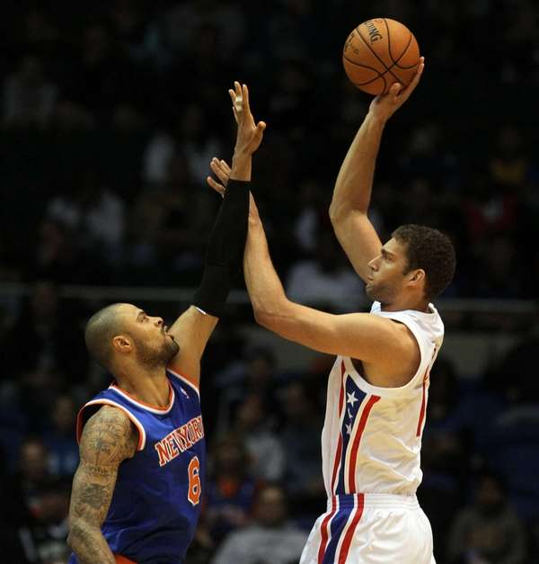 Brook Lopez shoots against Tyson Chandler during a