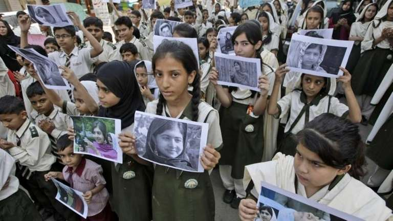Pakistani students hold pictures of 14-year-old schoolgirl Malala