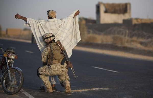 An Afghan National Civil Order Policeman searches a