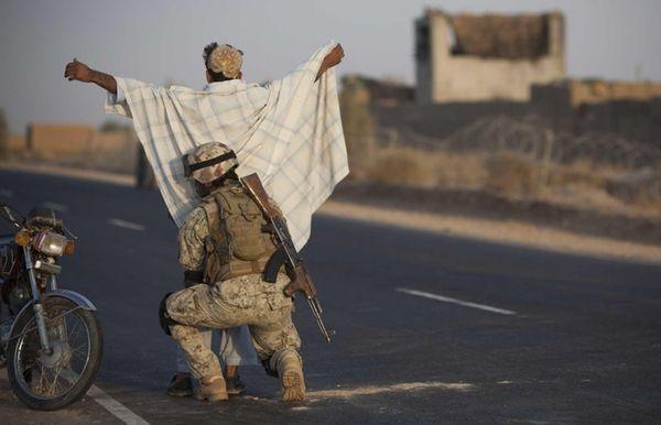 An Afghan National Civil Order Policeman searches a