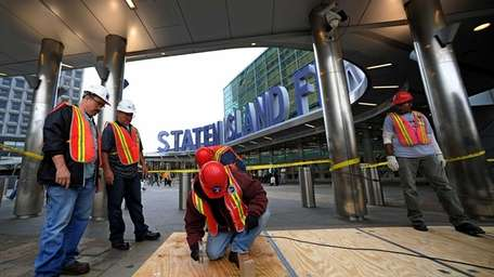 Metropolitan Transit Authority workers lay plywood over subway