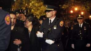 Officer Arthur Lopez's sister, Charo, is escorted into