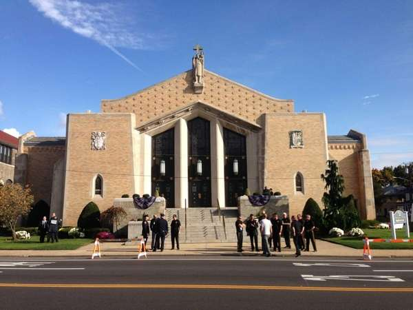 Police officers gather outside St. Christopher Church in