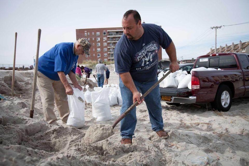 Michael Colon, right, 43, of Long Beach, sandbags