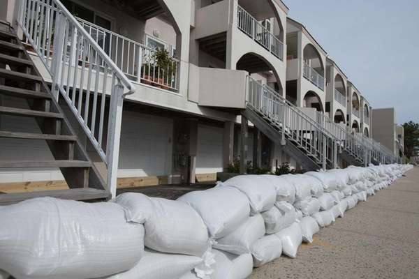 Sandbags are piled in front of homes on
