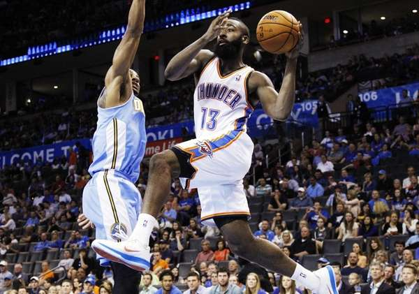Oklahoma City Thunder guard James Harden drives under