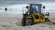 A bulldozer piles up sand on Long Beach