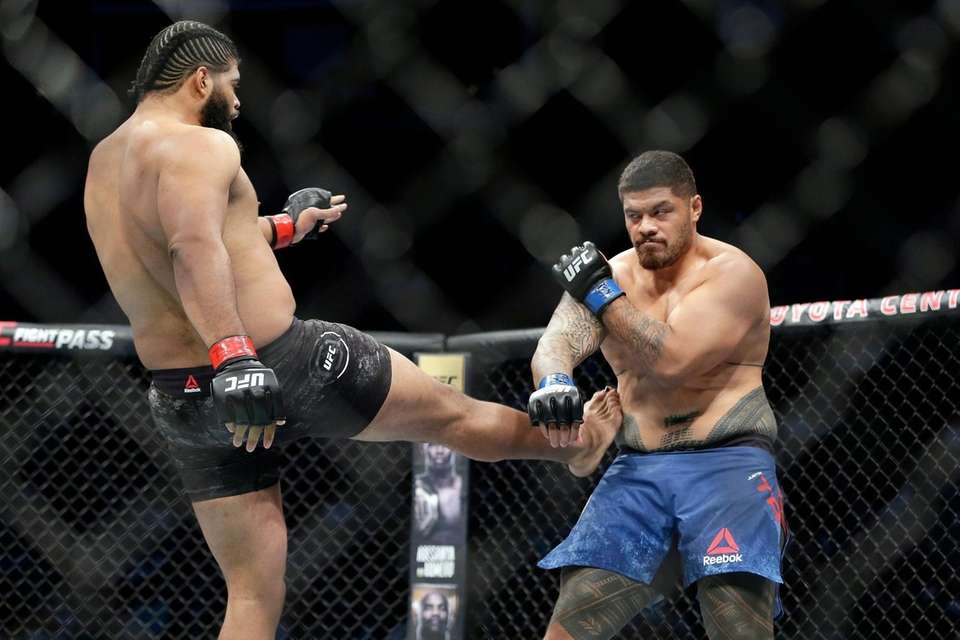 Juan Adams, left, has his kick blocked by