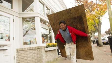 Ramone Rosas carries plywood for boarding storefronts in