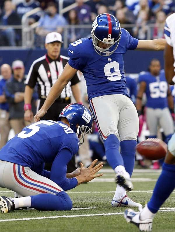 Giants punter Steve Weatherford holds as kicker Lawrence