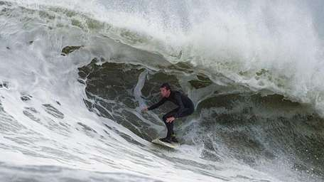 A surfer at Long beach catches a large