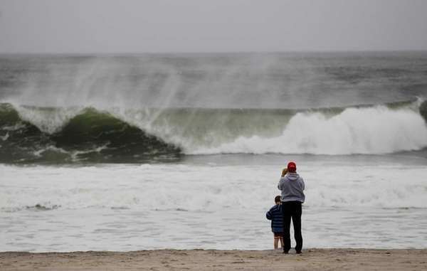 A man watches the waves as Hurricane Sandy