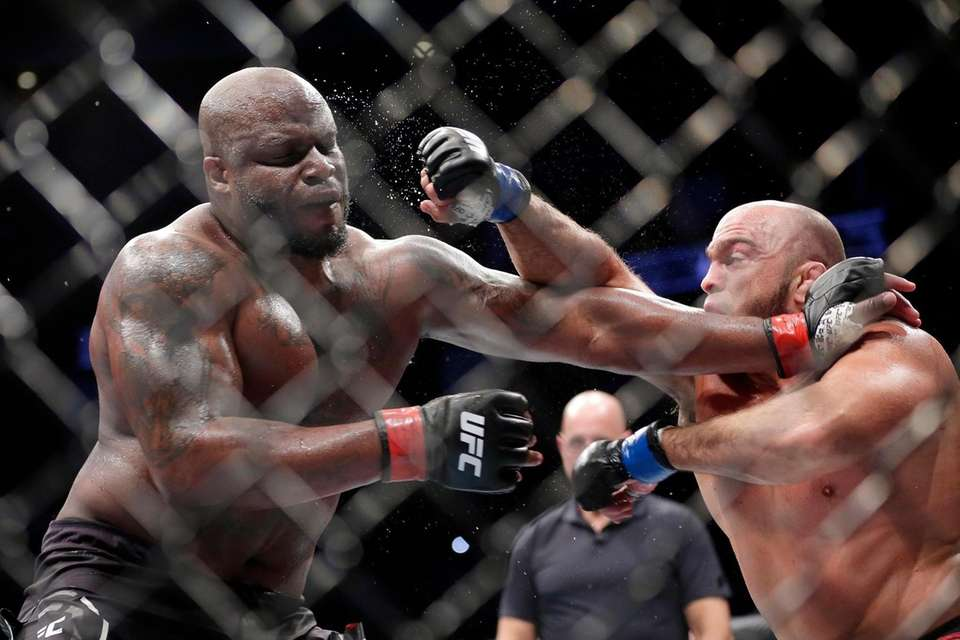 Derrick Lewis, left, takes a punch from Ilir