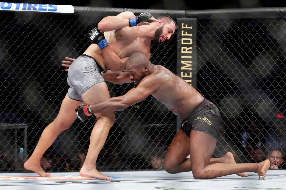Jon Jones, right, goes for a take down