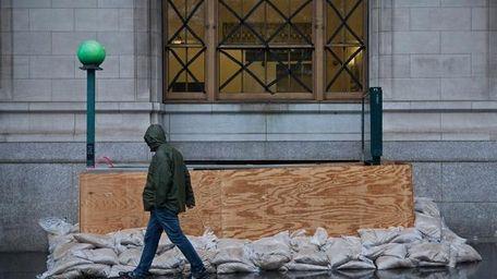 A man walks past a barricaded subway entrance